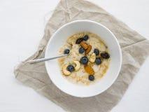 Porridge della farina d'avena con il mirtillo, il miele ed i dadi freschi Immagine Stock