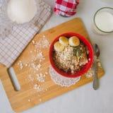 Porridge della farina d'avena della prima colazione con le banane, i semi, i dadi ed il latte Immagine Stock