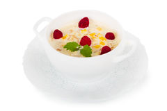 Porridge with fresh raspberries and peaches. In a white plate. Isolated on white Royalty Free Stock Photos