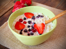 Oatmeal with  strawberry, blueberries and cranberry. Porridge with fresh strawberry, blueberries and cranberry Stock Photo