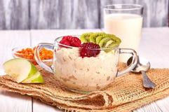 Porridge with fruit on wooden background stock image