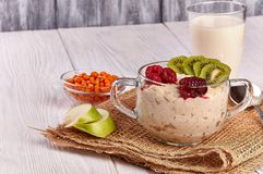 Porridge with fruit on wooden background stock images