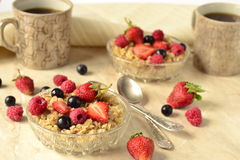 Porridge with grains, fresh berries in a glass bowl and tea Stock Images