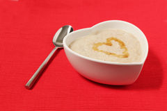 Porridge in a heart shape bowl on red background stock photos