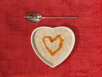 Porridge in a heart shaped bowl with honey Stock Image