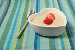 Porridge in a heart shaped bowl with strawberries Royalty Free Stock Photo