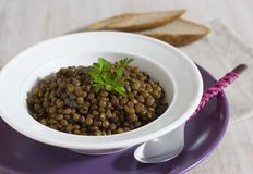 Porridge from lentil for breakfast. Grains are welded and seasoned with olive oil and parsley, contain vitamin B, vegetable protein and iron Stock Photo
