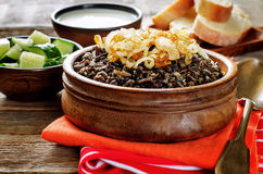 Porridge made with wild rice and black lentils with fried onions Stock Images