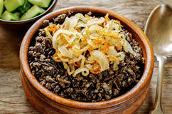 Porridge made with wild rice and black lentils with fried onions Royalty Free Stock Images