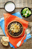 Porridge made with wild rice and black lentils with fried onions stock image