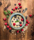 Porridge with milk , berries in rustic bowl on wooden background, top view Royalty Free Stock Photos