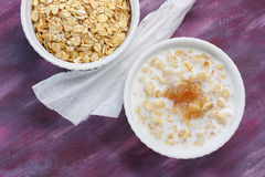 Porridge with milk and brown sugar and raw rolled oats Royalty Free Stock Image