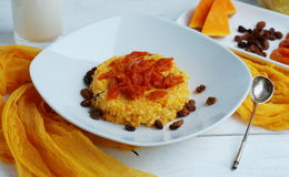 Porridge of millet cereal with a pumpkin. Raisins and dried apricots on a white background Royalty Free Stock Image