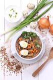 Porridge with champignons. Porridge with mushrooms in a ceramic bowl, fresh onions and sour cream on wooden white background Stock Images
