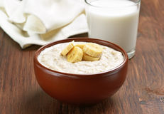 Porridge oats with banana slices and glass of milk Royalty Free Stock Photo