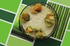Porridge pigro della farina d'avena, decorato con il physalis, su un fondo verde con le varie figure grafiche Fotografia Stock Libera da Diritti