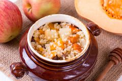 Porridge with pumpkin in a clay bowl. On a rustic wooden background stock photography