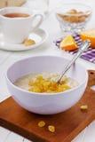Porridge with raisin in a bowl. On the white table Stock Photo