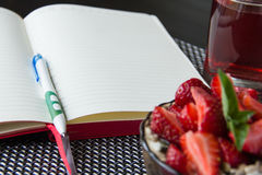 Porridge with strawberries and open food diary Royalty Free Stock Image