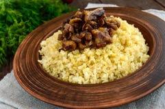 Porridge tradizionale orientale del grano - bulgur con le carni grasse arrostite dei pezzi, bacon in una ciotola dell'argilla fotografia stock