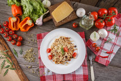 Porridge with vegetables in Italian. Risotto with vegetables. Still life with a dish and fresh vegetables on a wooden background. stock image