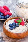 Porridge   in a wooden bowl with berries Royalty Free Stock Image