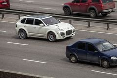 Porsche blanche de accord Cayenne expédiant sur la route vide Photographie stock