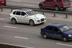Porsche branca de ajustamento pimenta de Caiena que apressa-se na estrada vazia Fotografia de Stock