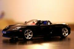 Porsche Carrera GT model racing car 1:24. Porsche Carrera GT sport car - die-cast metal model toy 1:24 scale, Black. Lateral view Royalty Free Stock Image