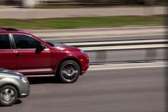 Porsche Cayenne rojo de lujo que apresura en la carretera vacía imágenes de archivo libres de regalías