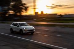 Porsche cayennepeper op snelheid met de zomerzonsondergang stock afbeeldingen