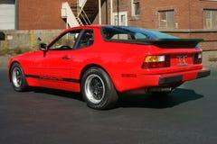 Porsche 944 i röd tillbaka sida framme av tegelstenfabriken royaltyfri fotografi