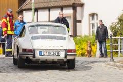 Porsche 911 kör längs en gata på en oldtimerfestival arkivfoton