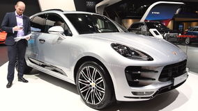 Porsche Macan compact crossover luxury SUV. On display during the 2017 European Motor Show Brussels. A man is inspecting the car stock video footage