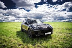 Porsche Macan is parked. On a fresh green spring grass. Moscow, Russia royalty free stock photos