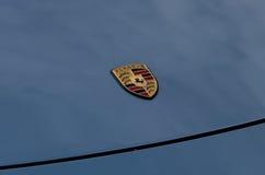Porsche znak na błękitnym samochodowym kapiszonie Zdjęcie Royalty Free