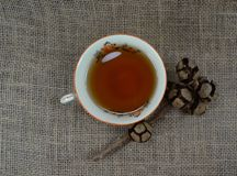 Porselain branco quente do copo de chá com a decoração na serapilheira e no fundo de madeira preto fotografia de stock royalty free