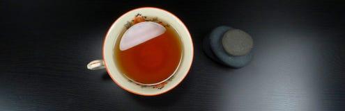 Porselain chaud de tasse de thé avec des pierres et décoration au fond en bois noir image stock