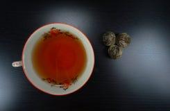Porselain quente do copo de chá com flores do chá em um teatime de madeira preto do fundo! imagem de stock
