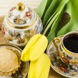 Porselein met gele tulpenbloemen en cake die wordt geplaatst Royalty-vrije Stock Fotografie