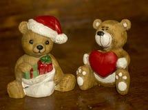 Porseleinfigarines dragen santa en een beer houdend een hart Stock Foto's
