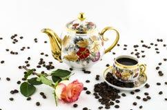 Porseleinkoffie (kop en kruik) wordt geplaatst met roze bloem en koffiebonen die Royalty-vrije Stock Fotografie