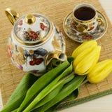 Porseleinkoffie met gele tulpenbloemen die wordt geplaatst Royalty-vrije Stock Foto