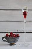 Porseleinkop met kersen en brandewijnglas Stock Fotografie