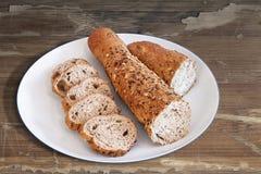 Porseleinplaat met het Integrale Bruine die Brood van Baguette in Plakken wordt gesneden Stock Afbeelding