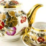 Porseleinthee en koffie met bloemmotief wordt geplaatst op wit dat Stock Foto's