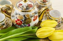 Porseleinthee en koffie met gele tulpenbloemen die wordt geplaatst Stock Foto