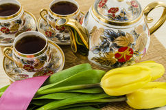 Porseleintheestel met gele tulpenbloemen Stock Fotografie