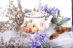 Porslinkokkärlet med te och lilan blommar på en vit tabell Fotografering för Bildbyråer