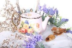 Porslinkokkärlet med te och lilan blommar på en vit tabell Royaltyfri Foto